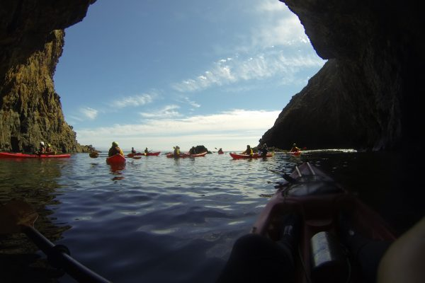 kayakers sitting outside the sea cave